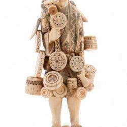 Statuetta Okimono in avorio di venditore ambulante con maschere, vasi e altri piccoli oggetti. Inciso e colorato.